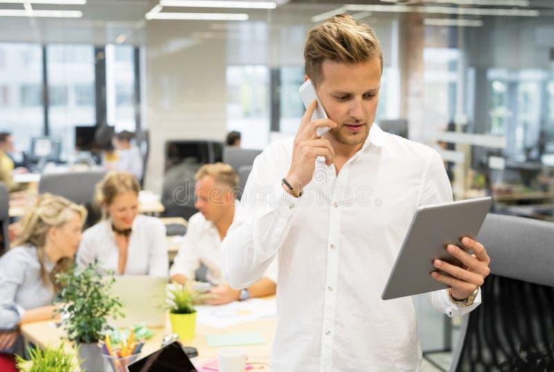 Homme dans le bureau ouvert parlant au téléphone et regardant le comprimé photos stock