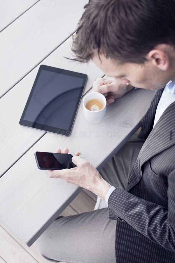 Homme dans le bureau utilisant le smartphone photographie stock libre de droits