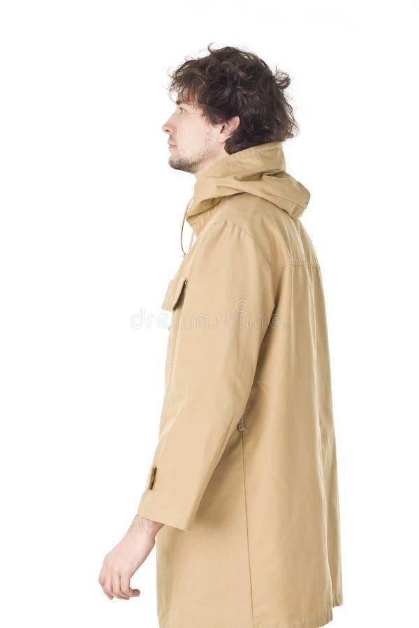 Homme dans le côté debout de manteau à l'appareil-photo images stock