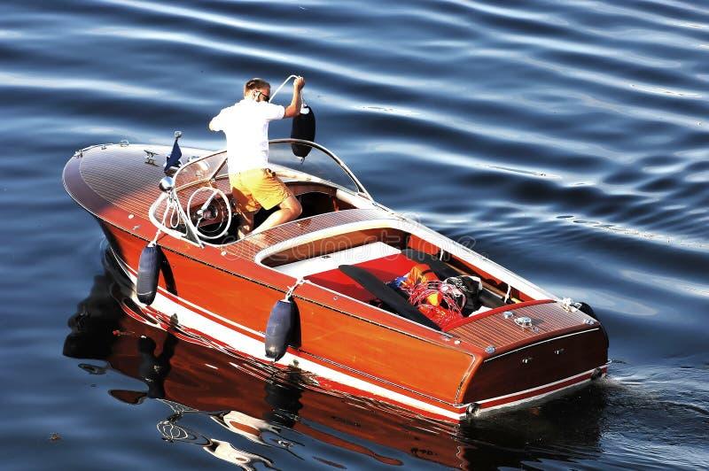 Homme dans le canot automobile en bois photographie stock