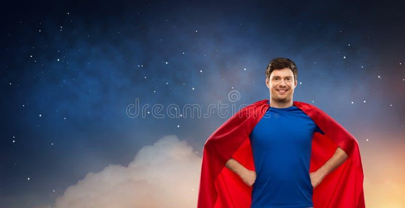 Homme dans le cap rouge de super h?ros au-dessus du ciel nocturne image libre de droits