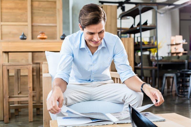 Homme dans le catalogue de lecture rapide de magasin de meubles image stock