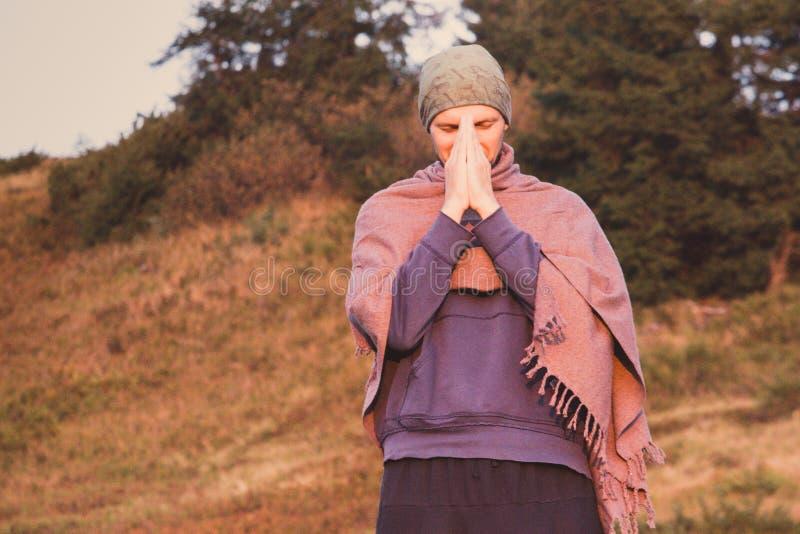 Homme dans le châle avec des mains de namaste priant en montagnes Concept de prière de lever de soleil Méditation de matin sur le photographie stock libre de droits
