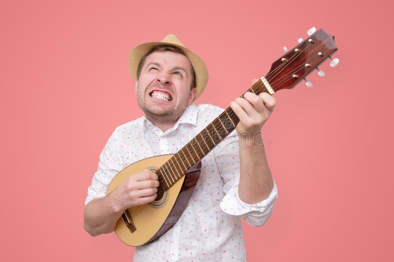 Homme dans le chapeau d'?t? jouant la guitare et chantant des chansons photos libres de droits