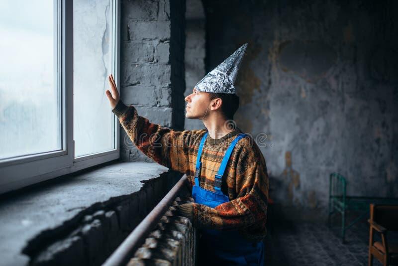 Homme dans le chapeau de feuille d'étain regardant la fenêtre, UFO images libres de droits