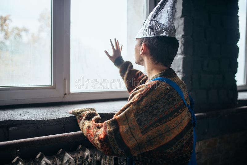 Homme dans le chapeau de feuille d'étain regardant la fenêtre, UFO photographie stock libre de droits