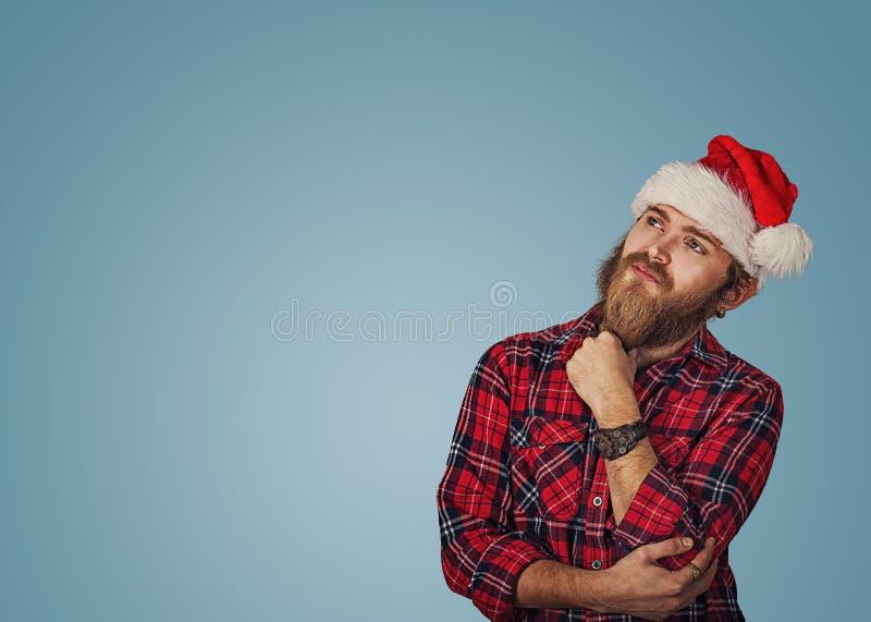 Homme dans le chapeau de Noël recherchant pensant photo stock