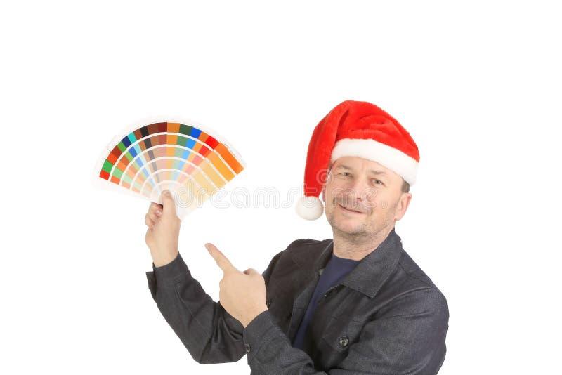 Homme dans le chapeau de Santa avec des échantillons de couleur. photographie stock libre de droits