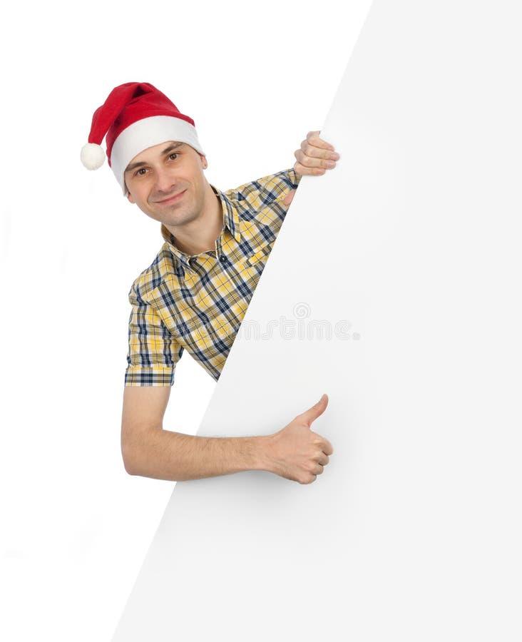 Homme dans le chapeau de Santa avec le panneau-réclame blanc photographie stock libre de droits