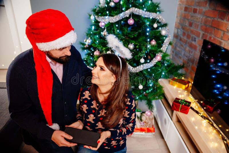 Homme dans le chapeau de Santa Claus étonnant son épouse avec un cadeau de Noël photos libres de droits