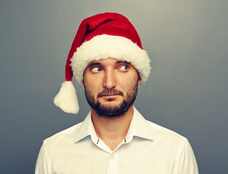 Homme dans le chapeau de Santa regardant quelque chose image libre de droits