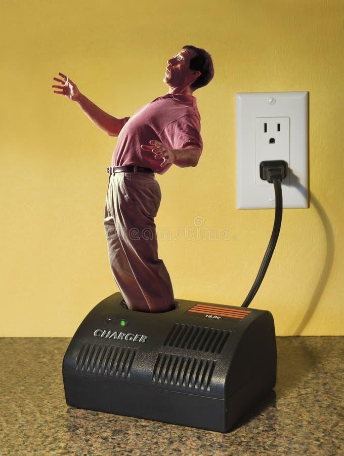 Homme dans le chargeur électrique image stock