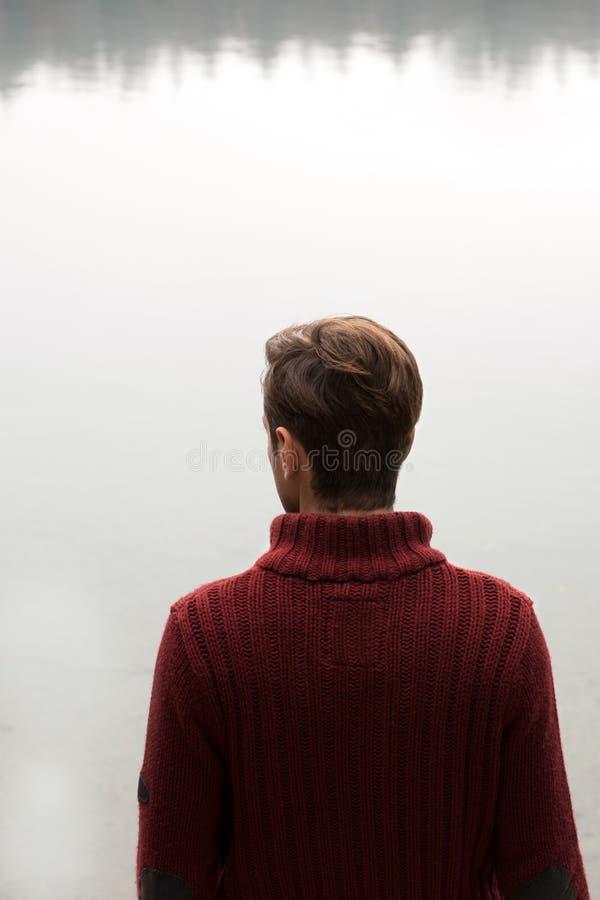 Homme dans le chemisier rouge foncé regardant le lac/pensant des hommes dans le pull rouge se tenant avec l'eau/meditat arrières  photo stock