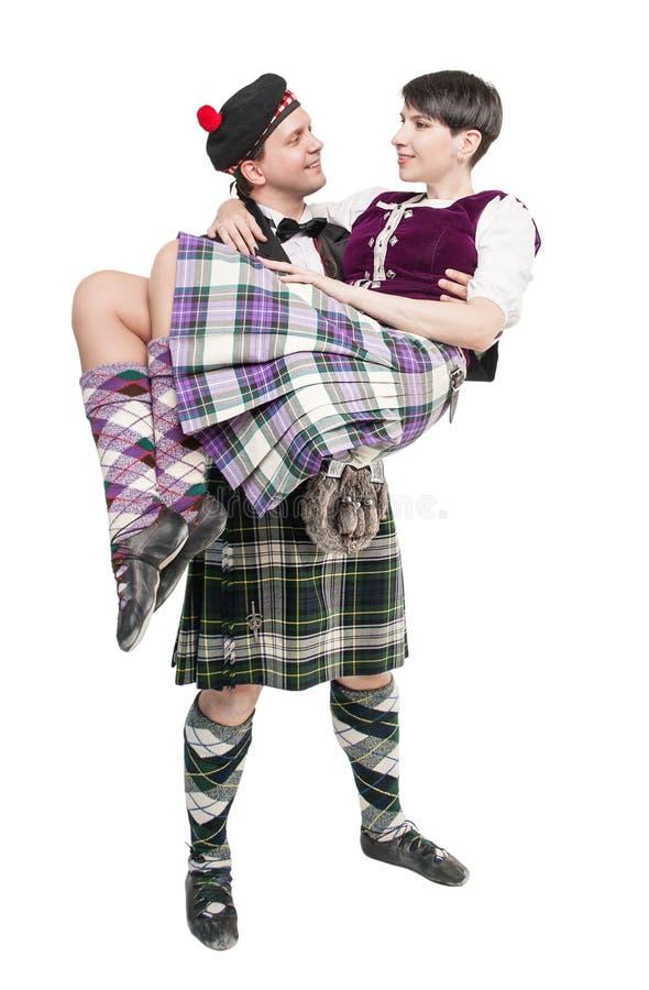 Homme dans le costume écossais de traditioanl tenant la femme sur des mains photo stock
