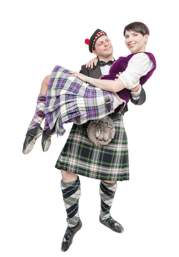 Homme dans le costume écossais de traditioanl tenant la femme sur des mains image libre de droits