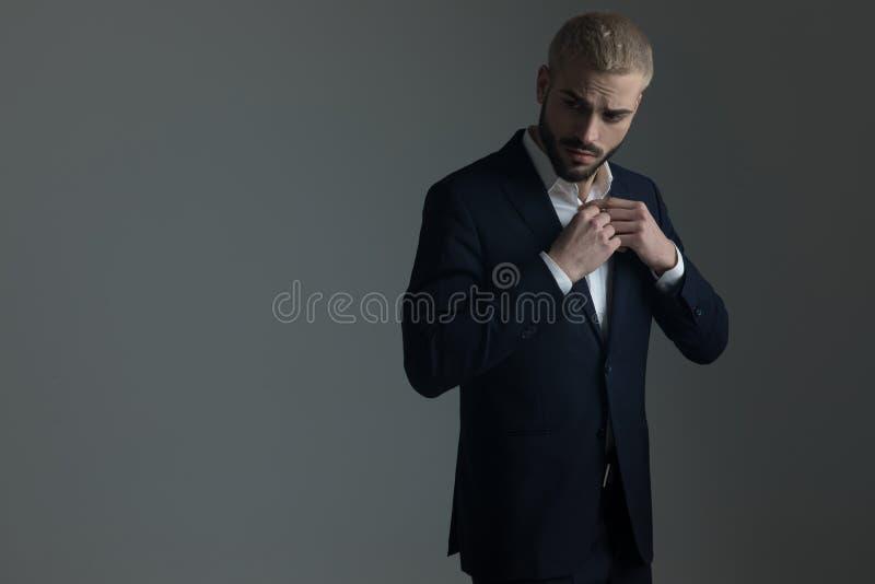 Homme dans le costume ajustant ses boutons sur sa chemise photographie stock libre de droits