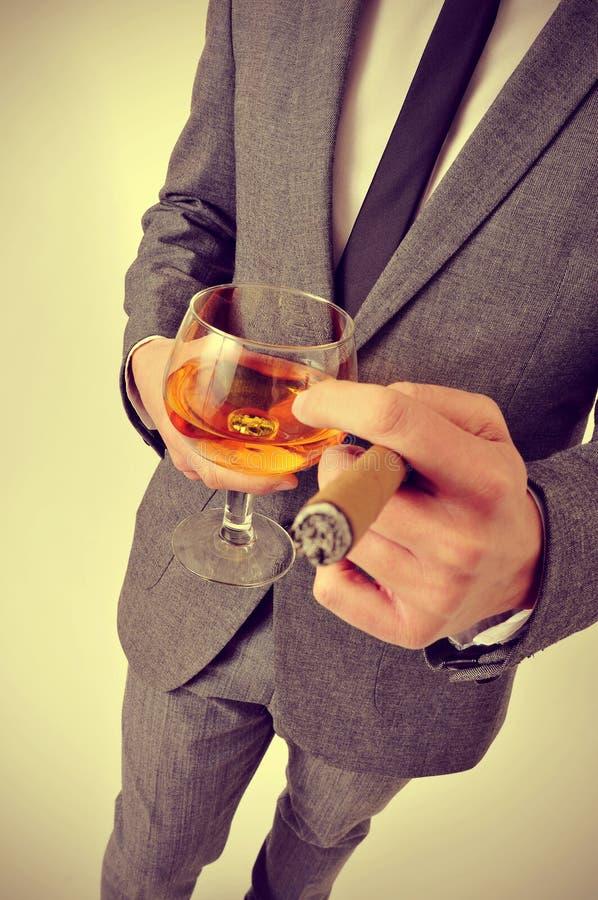 Homme dans le costume avec un cigare et un verre avec l'eau-de-vie fine image libre de droits