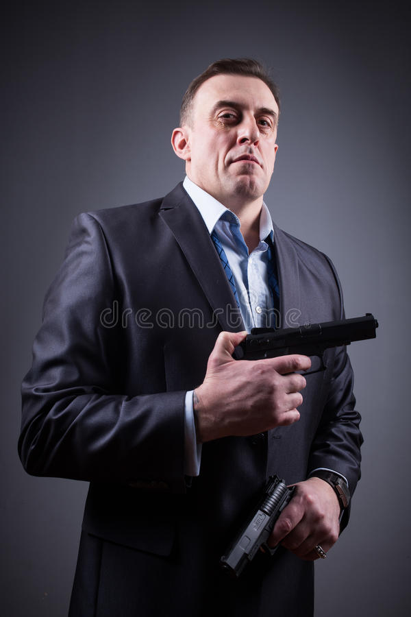 Homme dans le costume avec une arme à feu photo stock