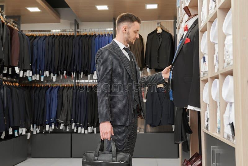 Homme dans le costume choisissant près du mannequin dans la boutique photographie stock libre de droits