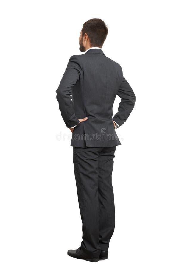 Homme dans le costume noir avec des mains sur la ceinture photo libre de droits