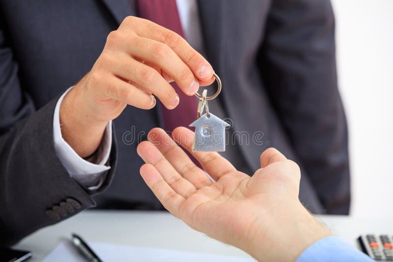 Homme dans le costume offrant une clé photos stock