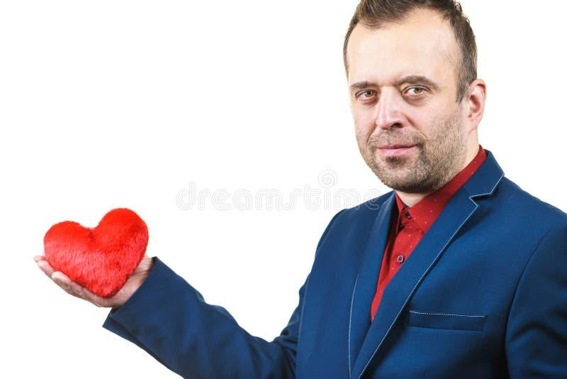 Homme dans le costume tenant le coeur photo stock