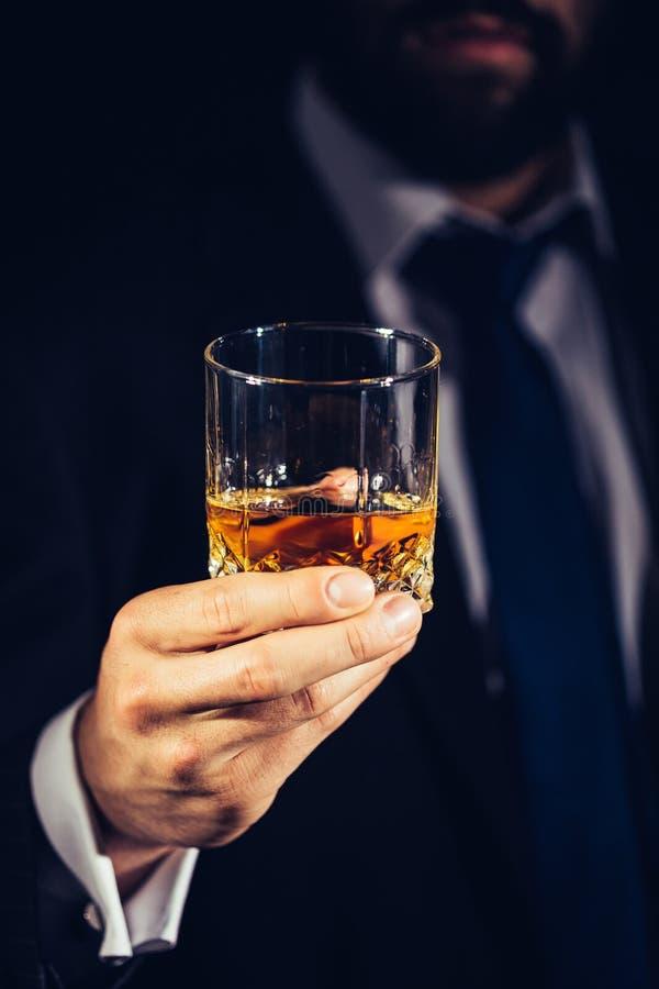Homme dans le costume tenant un verre d'alcool image stock