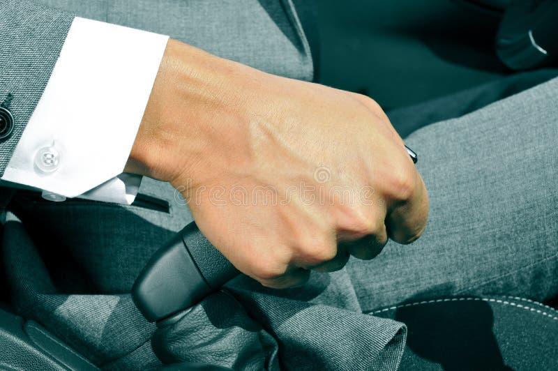 Homme dans le costume tirant le frein de main d'une voiture photo libre de droits