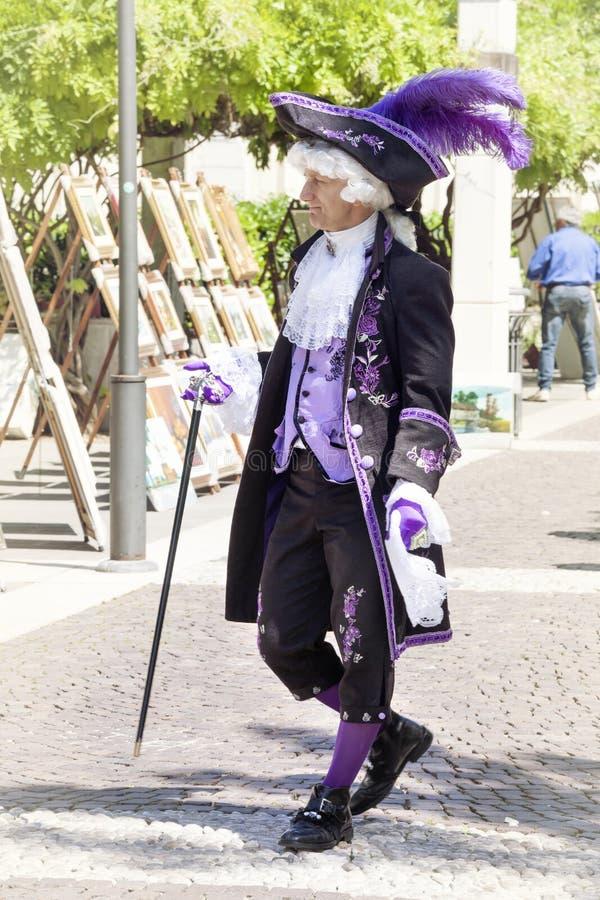 Homme dans le costume vénitien marchant dans la rue avec le bâton de marche photographie stock libre de droits