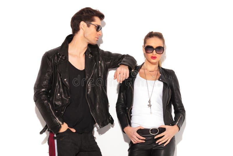 Homme dans le coude de penchement de veste en cuir sur le girlfriend& x27 ; épaule de s image stock