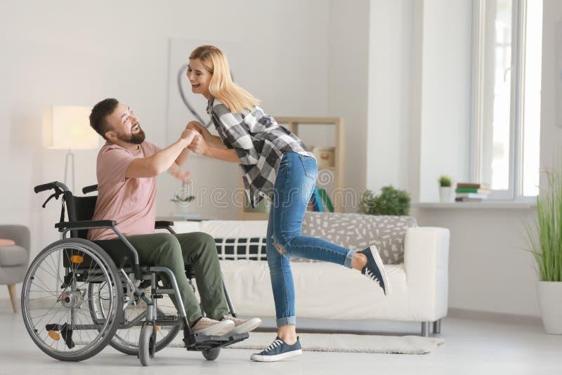 Homme dans le fauteuil roulant avec la belle femme dansant à la maison photos libres de droits