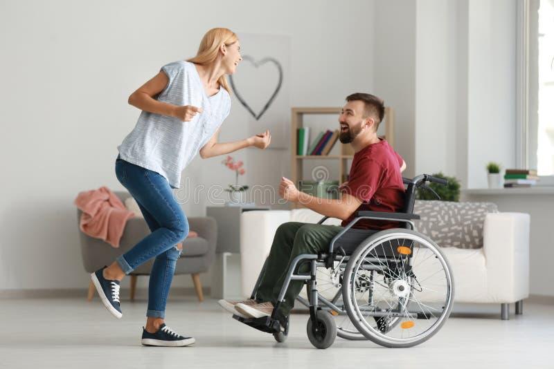 Homme dans le fauteuil roulant avec la belle femme dansant à la maison photographie stock