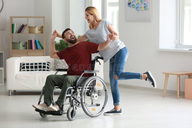 Homme dans le fauteuil roulant avec la belle femme dansant à la maison images stock
