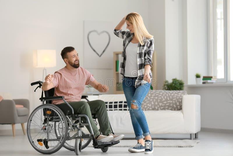 Homme dans le fauteuil roulant avec la belle femme dansant à la maison photo stock