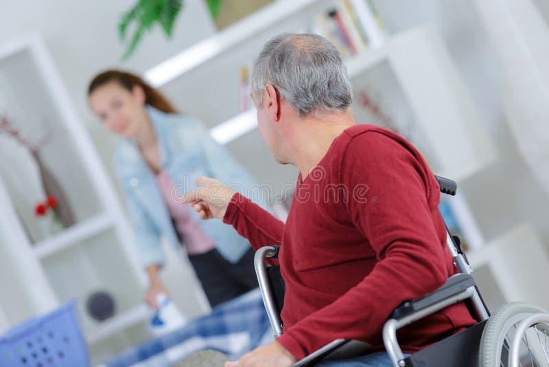 Homme dans le fauteuil roulant donnant des instructions à la jeune dame images stock