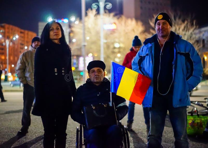 Homme dans le fauteuil roulant et ses amis à la protestation, Bucarest, Roumanie photographie stock