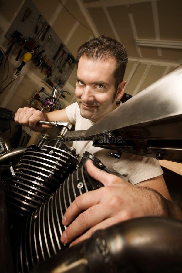 Homme dans le garage travaillant au motocycle photos stock