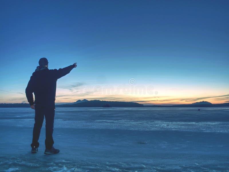 Homme dans le geste chaud de costume à l'horizon de matin Séjour de randonneur sur la glace photos stock