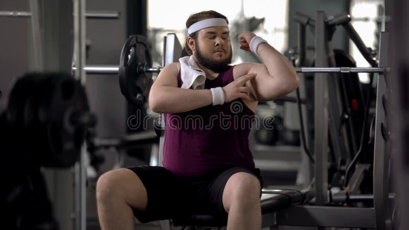 Homme dans le gymnase feignant pour être sportif, regardant le biceps, motivation de séance d'entraînement images stock