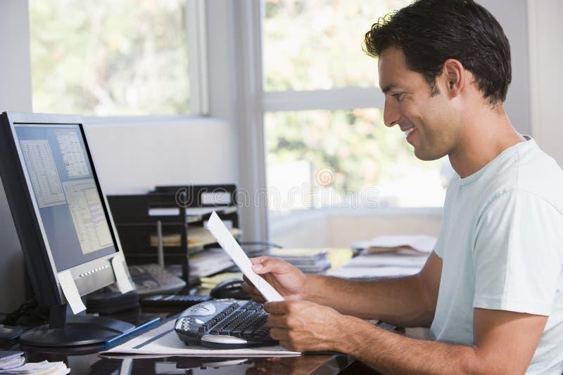 Homme dans le Home Office utilisant l'ordinateur photos libres de droits