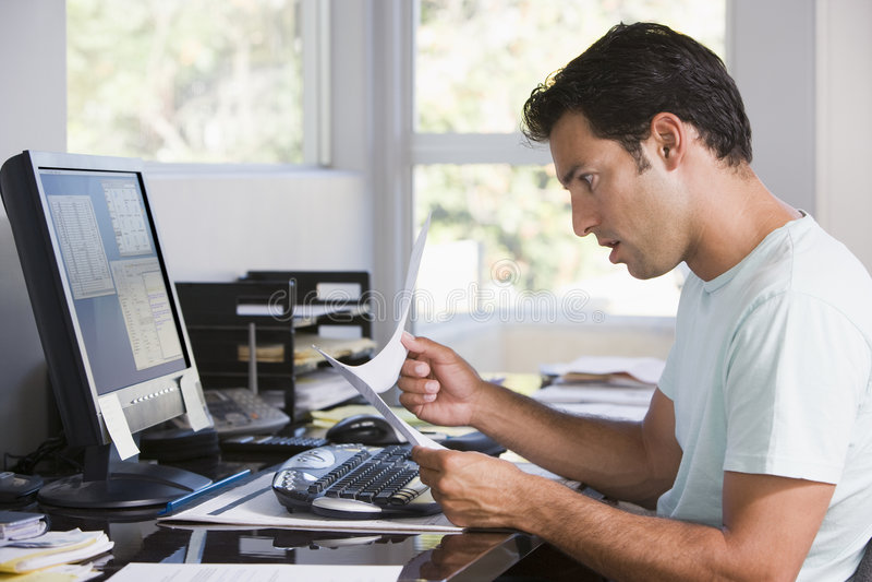 Homme dans le Home Office utilisant l'ordinateur image stock