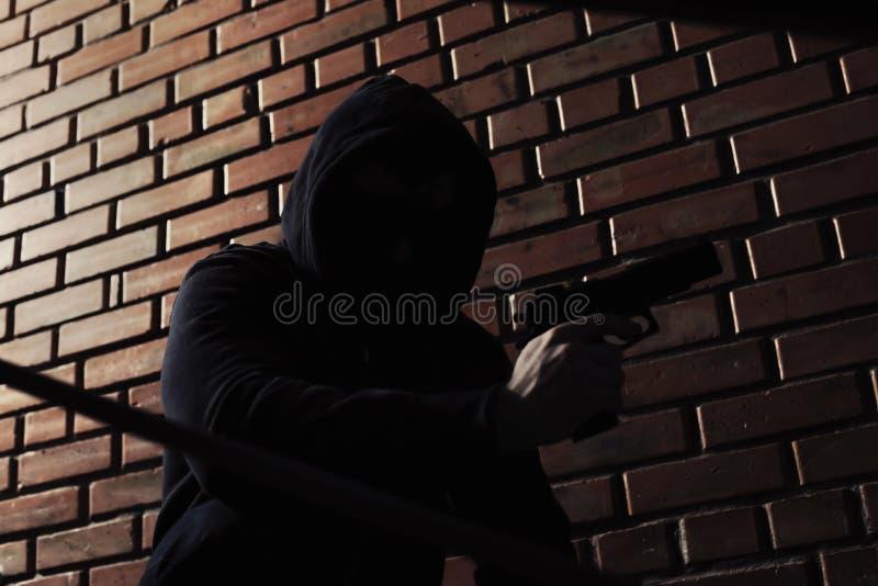 Homme dans le hoodie avec l'arme à feu Criminel dangereux photo libre de droits