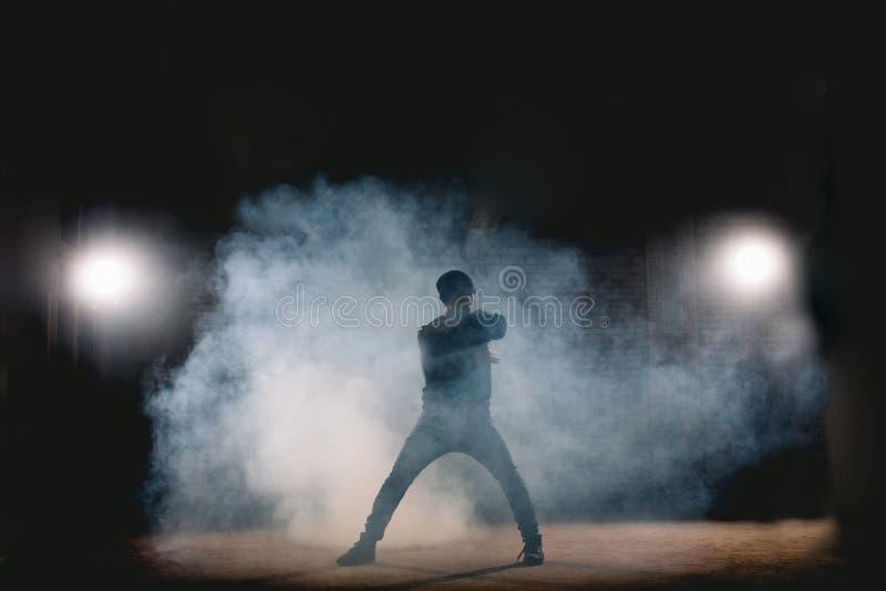 Homme dans le karaté de formation de vêtements de sport la nuit sur la rue image stock