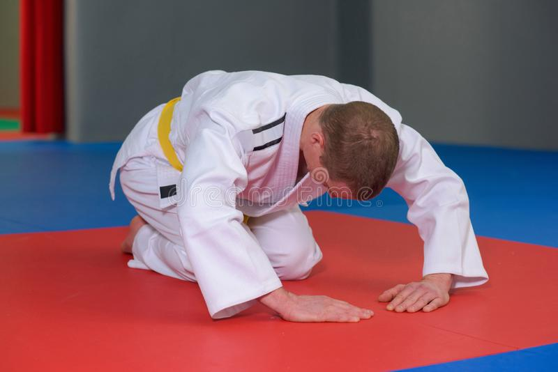 Homme dans le kimono en position cintrée sur le plancher images stock