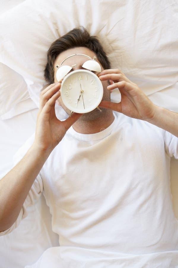 Homme dans le lit avec le réveil en Front Of Face photographie stock
