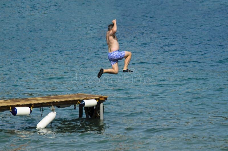 Homme dans le maillot de bain sautant dans la mer d'un pilier en bois portant les chaussures en caoutchouc noires photo libre de droits