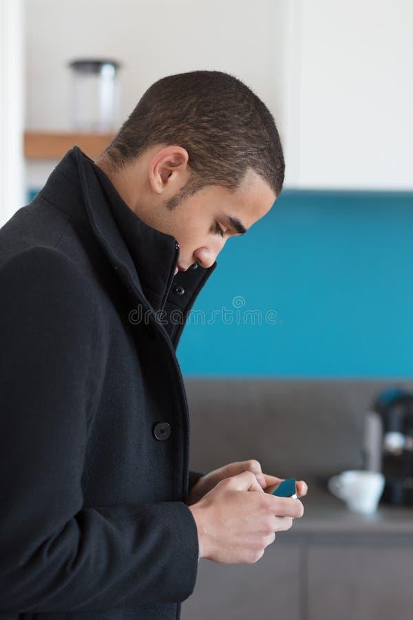 Homme dans le manteau noir regardant le téléphone portable photographie stock libre de droits
