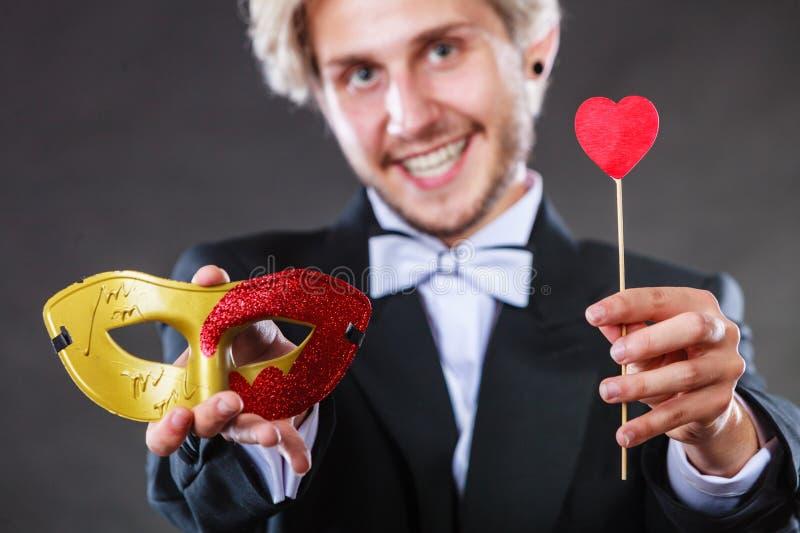 Homme dans le masque de carnaval avec le symbole d'amour de bâton de coeur photographie stock libre de droits