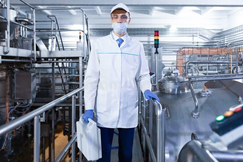 Homme dans le masque et robe longue avec une serviette à disposition se tenant sur des laitages d'une usine photographie stock