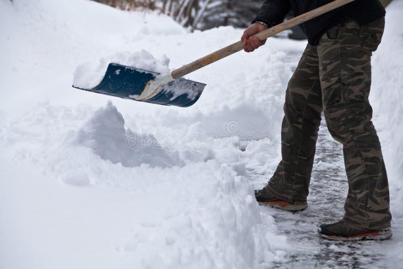 Homme dans le pantalon de camo dégageant la neige à sa maison photographie stock libre de droits